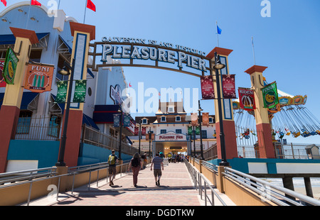 Tourists walking into Galveston Island Historic Pleasure Pier on sunny day - Stock Image