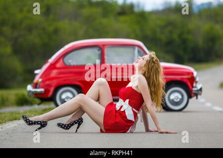 Young woman legs heels stiletto shoes Black with White dots smiling looking away up upwards - Stock Image