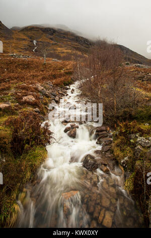 A waterfall cascades down the side of a mountain in autumn in Torridon, Scotland - Stock Image