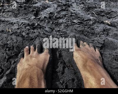 A pair of feet on top of black sand - Stock Image