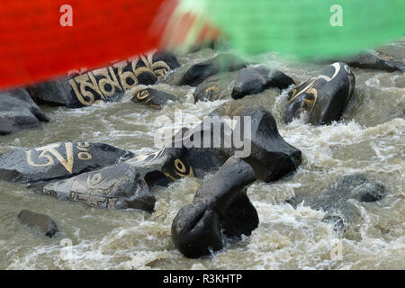 Rocks painted with prayer words and prayer flags in the river, Tagong, western Sichuan, China - Stock Image
