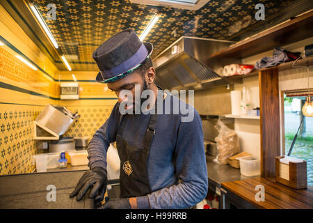 Man with hat and apron working in commercial kitchen of food truck - Stock Image