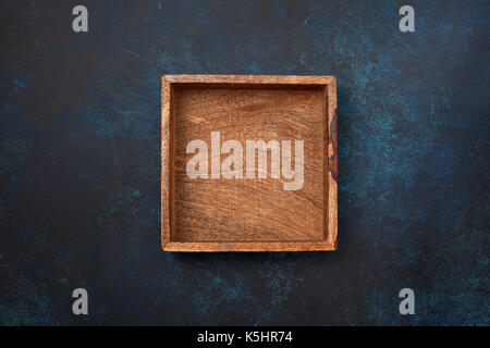 Empty wooden box on blue background. View from above. Copy space - Stock Image
