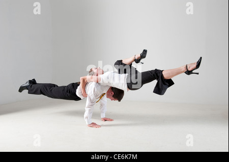 photograph of acrobatic businessman and women performing balancing act - Stock Image