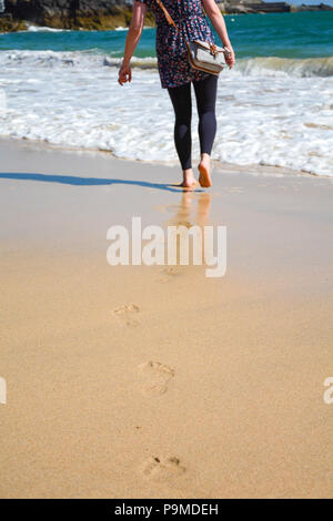 Woman walks barefoot on a beach, towards the sea in the distance leaving footprints on the wet sand, St Ives, UK - Stock Image
