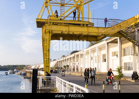 Yellow crane of the Belgrade Port on the Sava River and the Beton Hala (Concrete Hall) in the background. - Stock Image