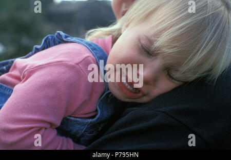 little girl crying on mother's shoulder - Stock Image
