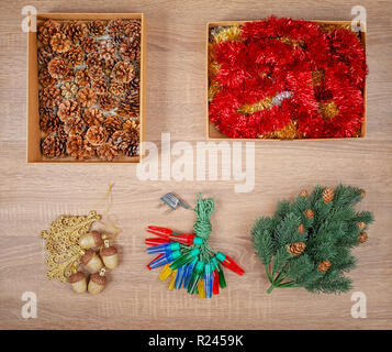 Traditional christmas tree decorations including baubles, fir cones, garland lights, glitter garland - Stock Image