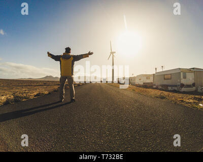 Standing man in the middle of the road opening arms for happy travel concept - alternative vacation with abandoned camping with caravans and high wind - Stock Image