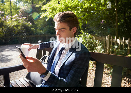 Young businessman sitting on park bench using smartphone - Stock Image