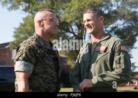 Lt. Gen. Robert F. Hedelund, II Marine Expeditionary Force commanding general, and Vice Adm. Andrew Lewis, commander U.S. 2nd Fleet, share a conversation after observing a visit, board, search and seizure with the 22nd Marine Expeditionary Unit at Camp Lejeune, N.C. Aug. 27, 2018. Hedelund and Lewis discussed how combining the capabilities of II MEF and the 2nd Fleet will strengthen joint-force partnership in the region and abroad. (U.S. Marine Corps photo by Pfc. Nicholas Guevara) - Stock Image