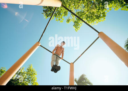 Beautiful young man training and working out in park. Handsome hispanic male athlete exercising with a chest and triceps routine for wellness. Latino  - Stock Image