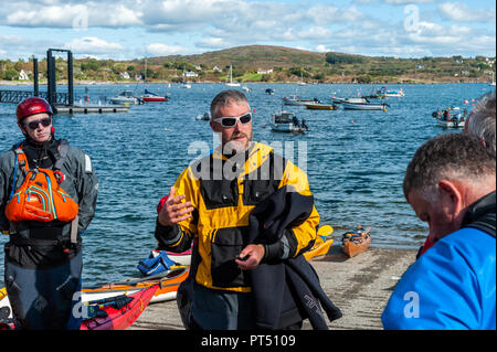 Schull, West Cork, Ireland. 6th Oct, 2018.  On a beautiful day in West Cork, a kayak instructor gives instructions before Association members paddle out into Schull Harbour. Today's activities culminate this evening in a dinner dance at the Schull Harbour Hotel. Credit: Andy Gibson/Alamy Live News. - Stock Image