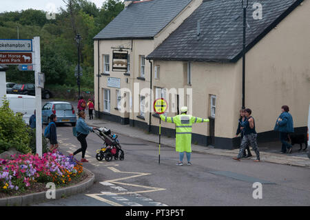 School crossing supervisor at work in a small English town. Hatherleigh, North Devon, England - Stock Image