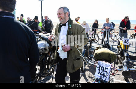 Brighton, UK. 24th March 2019. David Jones with his 1913 Ariel enjoys a drink after completing the 80th Anniversary Pioneer Run for pre 2015 veteran motorcycles . The run organised by the Sunbeam Motor Cycle Club begins on the Epsom Downs in Surrey and finishes on Madeira Drive on Brighton seafront Credit: Simon Dack/Alamy Live News - Stock Image
