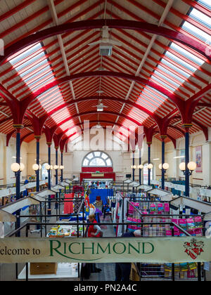 Interior of the covered market hall in Richmond North Yorkshire, with stalls selling antiques and trinkets - Stock Image