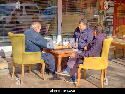 Old men playing backgammon at a cafe on old town street of Antalya, Turkey - January 3, 2019 - Stock Image