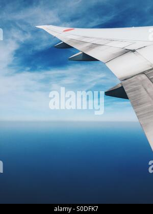 Window view of airplane wing of All-Nippon Airways Boeing 777-300 with blue sky and sea in background. - Stock Image