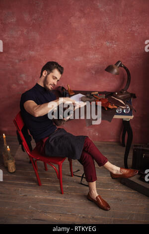 relaxed cheerful man sitting on the chair with crossed legs and cleaning the footwear, full length photo - Stock Image