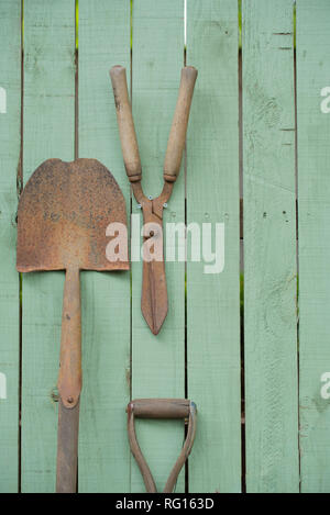 Old rusted gardening tools including a shovel and garden shears mounted on a timber garden fence painted green - Stock Image