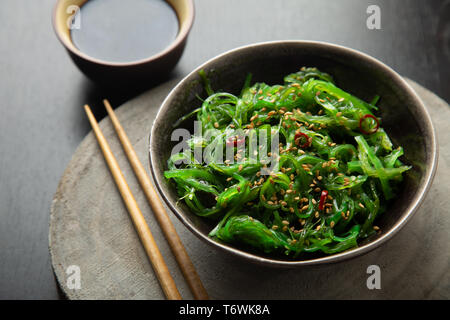 Wakame seaweed salad with sesame seeds and chili pepper in a bowl on a wooden slice - Stock Image