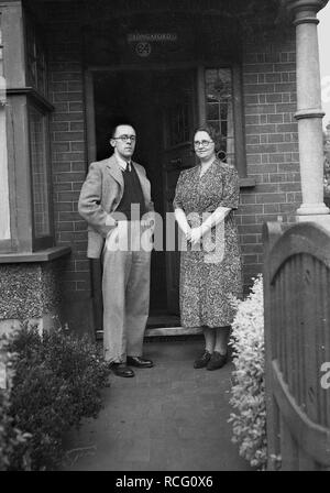 1950s, historical, a proud husband and wife dressed in the clothes of the era standing in formal pose outside on the path at the entrance to their house, England, UK. - Stock Image