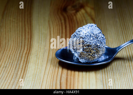 Ball of heroin wrapped in a tin foil ball resting on a silver teaspoon on a wooden textured surface. - Stock Image