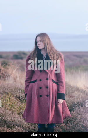 a young woman in a read coat is standing in the heather in winter - Stock Image