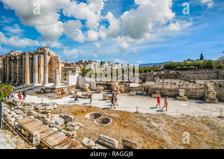 Tourists sightsee at the ancient West Wall of Hadrian's Library at the Roman Agora, with the popular Plaka district behind, in Athens, Greece. - Stock Image