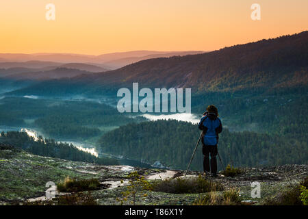 An outdoor photographer is photographing a beautiful sunrise in Nissedal, Telemark, Norway. - Stock Image