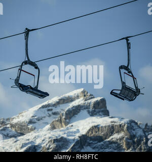 Skilift and chair lifts at ski resort  against snowy mountains in winter. Corvara in Badia in the Dolomites, South Tyrol, Italy. Blank copy space for  - Stock Image
