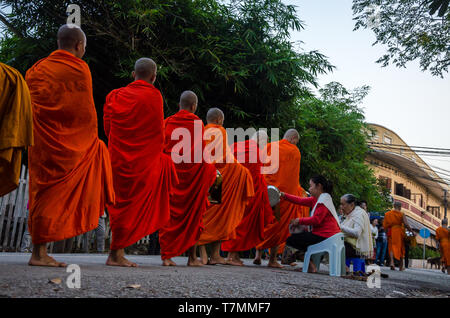 Monks during the Tak Bat, the morning ceremony where people offer food to monks, Luang Prabang, Laos - Stock Image
