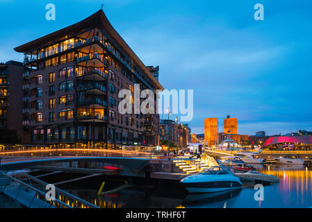 Oslo harbour, view at night of the harbour district (Aker Brygge) in central Oslo with the Town Hall building (Radhus) in the distance, Norway. - Stock Image