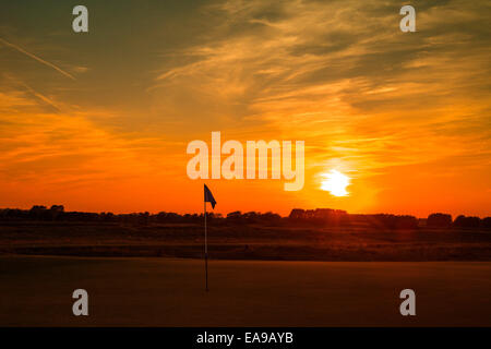 Golf flag against setting sun red sky over golf course - Stock Image