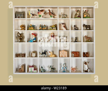 A box of small china figures and animals in a wall display unit - Stock Image