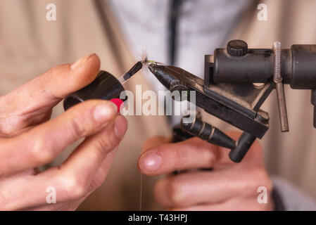 Close up of fisherman tying a fly for fishing . - Stock Image