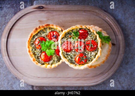 Mini Spinach Quiche served on a white plate - Stock Image