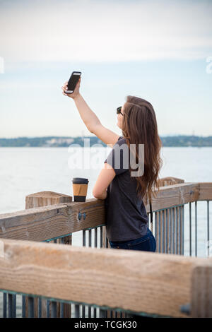 A pretty young millennial brunette woman with a coffee taking a selfies on a ocean boardwalk. - Stock Image