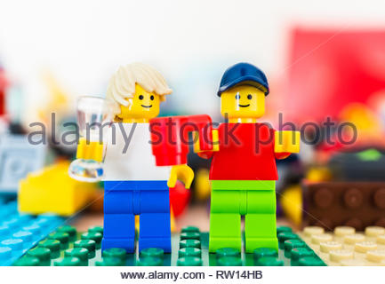 Poznan, Poland - February 15, 2019: Two Lego man figures standing next to each other and holding a drink celebrating. - Stock Image