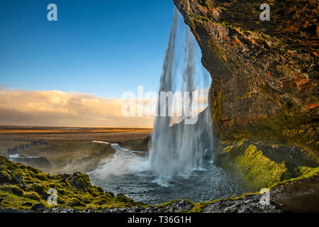 The famous Seljalandsfoss where you can walk completely behind this large waterfall. - Stock Image