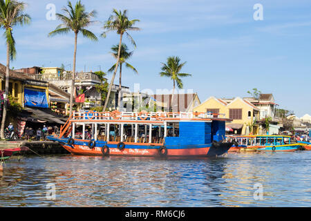 View across water to traditional tourist sampans boats moored along Thu Bon River in old quarter of historic town. Hoi An, Quang Nam Province, Vietnam - Stock Image