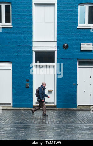 A man walking past a house painted blue and white in Clink Street in London. - Stock Image