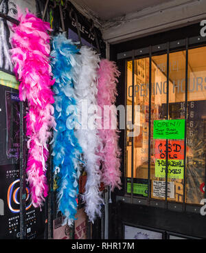 Feather boas hand outside the door of a curiosity shop selling herbal mixes, oils and other smoking accessories . - Stock Image