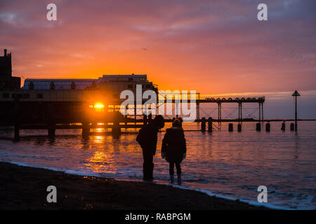 Aberystwyth Wales, UK. 03rd Jan, 2019. UK Weather: At the end of a grey dull and cold January day the sun makes a brief appearance as it sets over the Royal Pier in Aberystwyth on the Cardigan Bay coast of west Wales.Photo Credit: keith morris/Alamy Live News - Stock Image