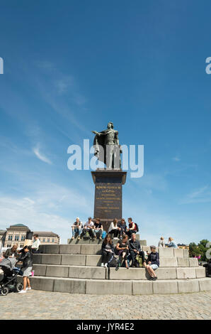 People sitting on the steps of a bronze statue of King Gustav III in Stockholm, Sweden on a sunny day - Stock Image