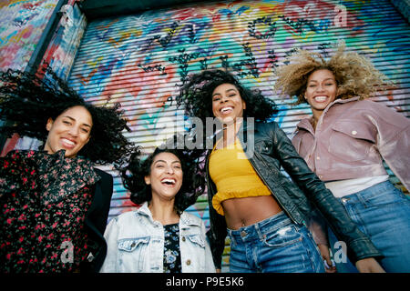 Low angle view of four young women with curly hair standing in front of shutter covered in colourful graffiti, smiling at camera. - Stock Image