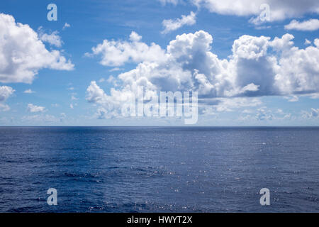 Blue sky, clouds and tranquil water at sea with horizon - Stock Image