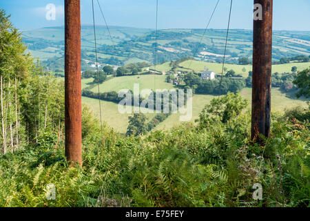 Electricity power pylon poles with cables extending across idyllic  English valley countryside - Stock Image