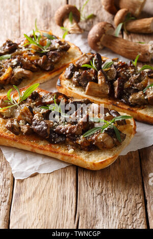 Delicious ciabatta with fried porcini mushrooms, onions, thyme and parmesan cheese closeup on the table. vertical - Stock Image
