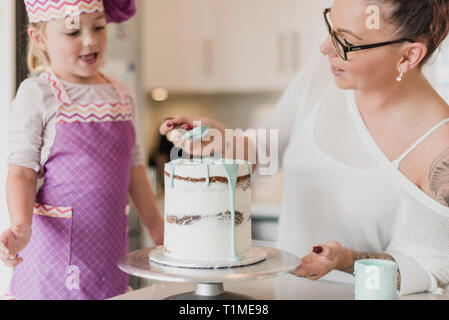 Mother and daughter decorating cake - Stock Image